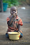Displaced by war, a boy savors the last of his porridge in the Makpandu refugee camp in Southern Sudan, 44 km north of Yambio, where more that 4,000 people took refuge in late 2008 when the Lord's Resistance Army attacked their communities inside the Democratic Republic of the Congo. Attacks by the LRA inside Southern Sudan and in the neighboring DRC and Central African Republic have displaced tens of thousands of people, and many worry the attacks will increase as the government in Khartoum uses the LRA to destabilize Southern Sudan, where people are scheduled to vote on independence in January 2011. Catholic pastoral workers have accompanied the people of this camp from the beginning. NOTE: In July 2011 Southern Sudan became the independent country of South Sudan.