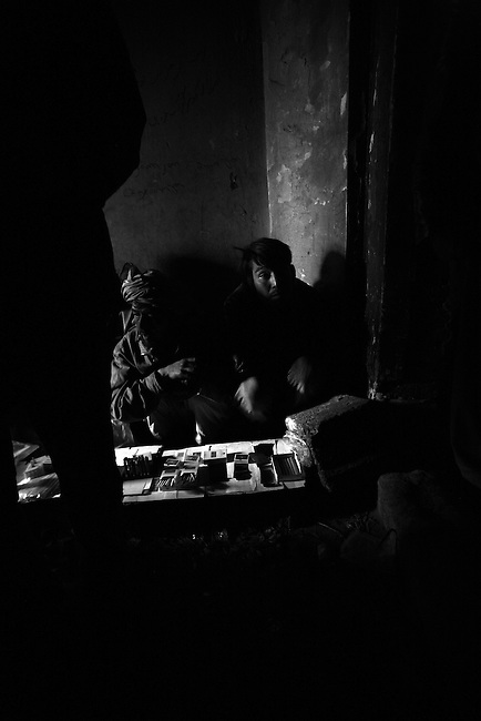 A man sells cigarettes and drug-smoking paraphernalia inside the ruins of the former Soviet Cultural Center in Kabul, Afghanistan. As many as 2,000 opium and heroin addicts gather each day to get high inside the derelict structure, which was almost completely destroyed during the 1992-1994 civil war. Feb. 2, 2009.