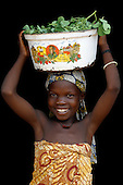 Girl carrying greens in a metal pan on her head, Lagos, Nigeria