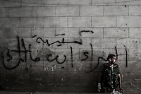 "An opposition fighter sniper leans against a wall tagged in arabic ""Qatabee Al Bara Eben Malek"" which is the name of the battalion that liberated the area, as he smokes a cigarette after a skirmish with the Syrian army at Bastan Basha residential neighborhood in the hub of Aleppo City."