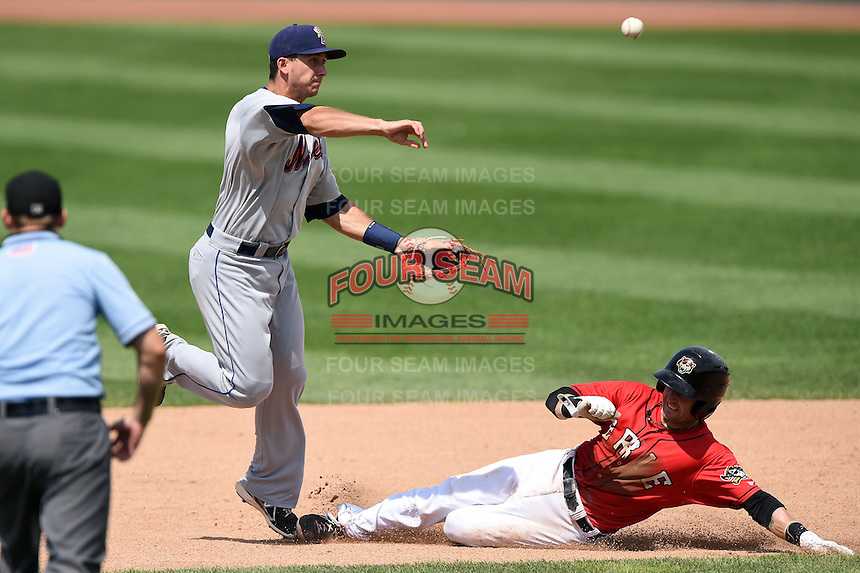 Binghamton Mets shortstop T.J. Rivera (5) turns a double play as Craig Albernaz (1) slides in during a game against the Erie Seawolves on July 13, 2014 at Jerry Uht Park in Erie, Pennsylvania.  Binghamton defeated Erie 5-4.  (Mike Janes/Four Seam Images)