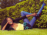 Laughing young african american woman in colorful clothes lying on green grass