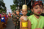 "Kids line up for the Dayurejo conservation carnival. Sign at back reads "" Together we preserve tradition and culture"""