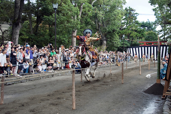 "A participant dressed in traditional attire fires his arrow at a target during the ""yabusame-shinji"" mounted archery ritual on the 3-day Reitaisai grand festival in Kamakura, Japan on  16 Sept. 2012.  Archers ride at speed and attempt to hit three targets along a 250-meter course erected inside the shrine grounds. Photographer: Robert Gilhooly"