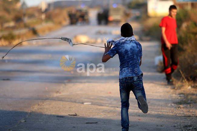A Palestinian protester uses a slingshot during clashes with Israeli security forces earby the Jalazoun refugee camp and the Jewish settlement of Beit El, north of Ramallah, after a demonstration in reaction to the death of a Palestinian toddler who was burned in an arson attack by suspected Jewish settlers on two homes in the occupied West Bank on July 31, 2015. Photo by Shadi Hatem
