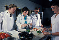 Team of food technicians examine fresh vegetables.