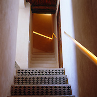Dark green tiled steps lead up to a second concrete staircase with a fibre-optic handrail