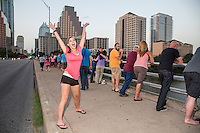 Cheerful attractive Austin woman wavers her hands with excitement on the Congress Ave. Bat Bridge in downtown Austin, Texas.