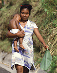 A Palauan carries her sleeping child. The palm leaf was used as an umbrella to shade the child from the hot afternoon sun. The island republic of Palau has been everything from a Japanese military base to a U.S. Trust territory it now seeks profitable indignity as a plush Pacific resort..The Republic of Belau lies 1,300 kilometers, southwest of Guam, and 600 kilometers east of the Philippines. (Jim Bryant Photo).....