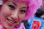 A woman tourist wearing a pink curly wig in the grounds of Wakamiya Hachiman gu shrine during the Kanamara matsuri, Kawasaki Daishi, Japan April 5th 2009