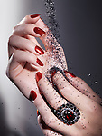Black sand falling on woman's hands with bright red nail polish and a red stone ring
