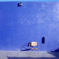 On the sunny patio of this house in Mexico a round garden chair is situated against a blue-painted walls