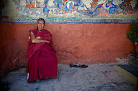 A Buddhist monk sits on the porch of a monastery in Nubra,  Ladakh.