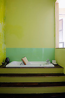 A sunken bath with a built-in jacuzzi is reached via a set of wooden steps in this yellow-painted bathroom