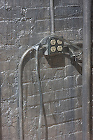 A steel junction box blends into a silver painted wall.  Piping and conduit run along the wall.
