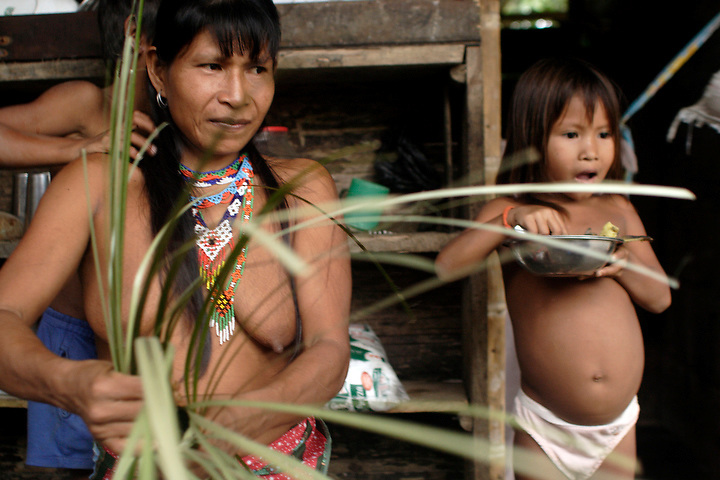 NUQUÍ, EL CHOCO, COLOMBIA -- DECEMBER 14:  An indigenous woman weaves a basket from palm leaves while her children watch in a village near the town of Nuqui on December 14, 2005. Nuquí is a small town on Colombia's isolated and untamed Pacific coast, an area sandwiched between endless miles of trackless rainforest and the Pacific Ocean. (Photo by Dennis Drenner/Aurora).