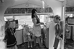 Interior of gypsy caravan, kitchen area there is no running water as it is concidered unlucky. Mother two daughter and father. The Derby Day horse race, Epsom Down England. 1974