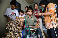 Disabled men and women processing dried water hyacinth stems for use as a material to make sandals, Makassar, Sulawesi, Indonesia.