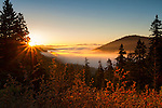 Idaho, North, Bonner County, Clark Fork. Rays of sun shine over the fog and trees of the Coeur d'Alene Mountains in autumn.