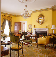 The primrose yellow drawing room, elegantly appointed with antique furniture upholstered in green and gold fabrics