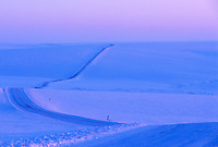 Ice covered James Dalton Highway (Haul Road) stretches across the snow covered Arctic coastal plains of Alaska.