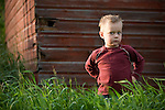 A young boy stands in a grassy field on a prairie farm in Saskatchewan, Canada.
