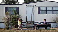 Children play in the garden of a trailer park, in Garden City, Kansas. The area is home to many migrant workers who have come to the town to work at the Tyson meat packing plant. The Tyson facility kills and processes between five and six thousand beef cattle every day. Kansas dominates the American beef industry, producing 25% of all beef raised in the USA. However, the industry is heavily dependent on cheap immigrant labour.