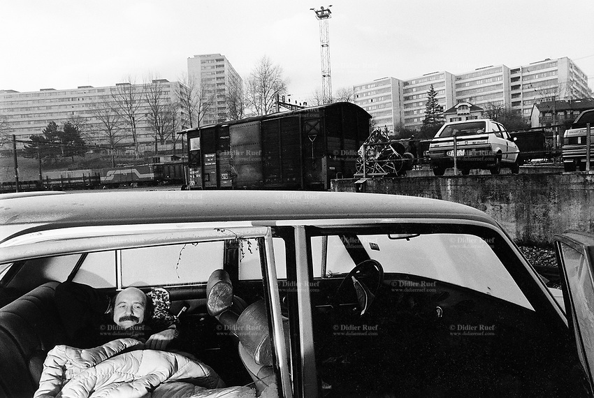 """Switzerland. Geneva. Poverty in Geneva. Ramon, 50 years old, is unemployed and homeless. He sleeps outside in a derelict car near the freight railway station """"La Praille"""". © 1989 Didier Ruef"""