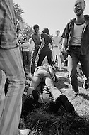 28 Jun 1970, Manhattan, New York City, New York State, USA. Two men lie on the ground in Central Park and kiss for the kissing contest as one man in the crowd laughs during New York's first Gay Pride celebration.