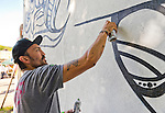 "Huntington, New York, U.S. 24th August 2013. MASPAZ, world renowned street artist FEDERICO FRUM from Washington DC, is painting black and white graffiti on the back of the Huntington Arts Council building, during the the art event ""Off the Walls"" Block Party, by SPARKBOOM, a project the council created to help emerging artists, showcase talents, and help its artistic family network. Mas Paz was born in Bogata Columbia and adopted from an orphanage when he was one; and he founded a charitable foundation to help the orphanage and other causes."