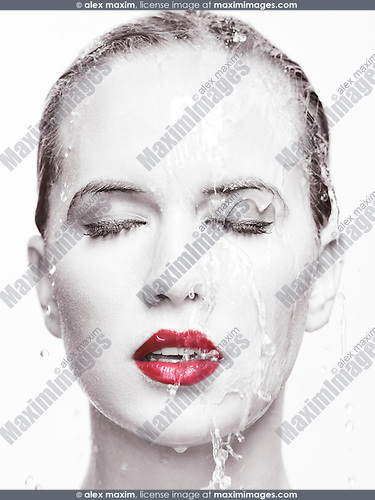 Artistic beauty portrait of a woman face with red lipstick with water running over it. Isolated on white background. Selective black and white.
