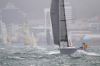 Karma Police sailed by Rob Shaw and Ben Costello leaves the  Wellington restart of Round North Island two-handed yacht race amid a shower of spray. Wellington, New Zealand. 2 March 2011. Photo: Gareth Cooke/Subzero Images
