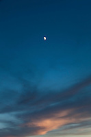 Left of the sunset, south of the big show, the waxing gibbous moon appears in a deep blue sky above painted clouds.