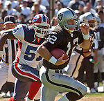 Buffalo Bills linebacker Takeo Spikes (51) chases Oakland Raiders quarterback Rich Gannon (12) on Sunday, September 19, 2004, in Oakland, California. The Raiders defeated the Bills 13-10.