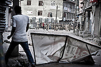 A Kashmiri Muslim protester walks by a sign used as shield during a street protest with paramilitary Indian forces and police in downtown Nowhatta area of Srinagar. The outcries against Indian rule are quite often held by stone-throwing youth in the disputed territory of Kashmir, where anti-India sentiment runs deep among the majority Muslim population. Srinagar, Indian administrated Kashmir.