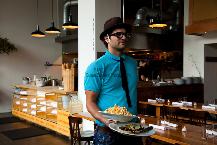 Clyde Common restaurant located next to the Ace Hotel in downtown Portland, Oregon opened in 2007 by Nate Tilden and Matt Piacentini, is a European style tavern.  Waiter Andrew holds the popcorn with pimenton and the flatbread of the day.