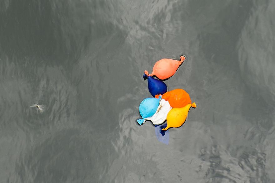 Nederland, Colijnsplaat, 2 aug 2013<br /> Ballonnen in water. Al een stuk leeggelopen ballonnetjes in het water van een haventje in Zeeland. Ballonnen, ook van biologisch afbreekbaar materiaal, breken langzaam af en worden vaak door zeevogels opgegeten.<br />  <br /> Foto(c): Michiel Wijnbergh