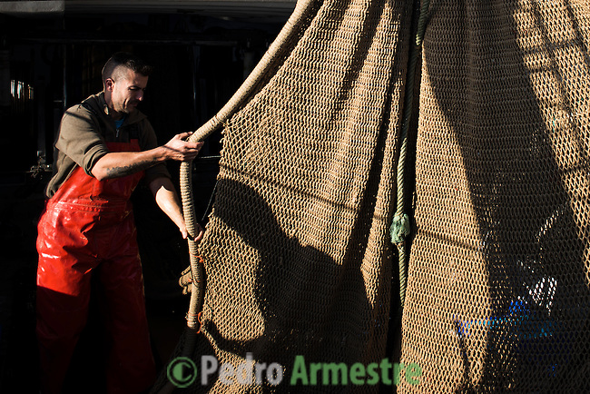"""A fisherman checks laces a net on a fishing boat off the coast of Villajoyosa on November 4, 2015. Ecoalf, a Spanish Madrid-based firm founded in 2010, has already launched """"a new generation"""" of clothes and accessories made from plastic bottles, old fishing nets and used tires found on land.  © Pedro ARMESTRE"""