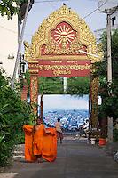 Phnom Penh, Cambodia. Monk at Wat Ounalom, city panorama photo in the background.