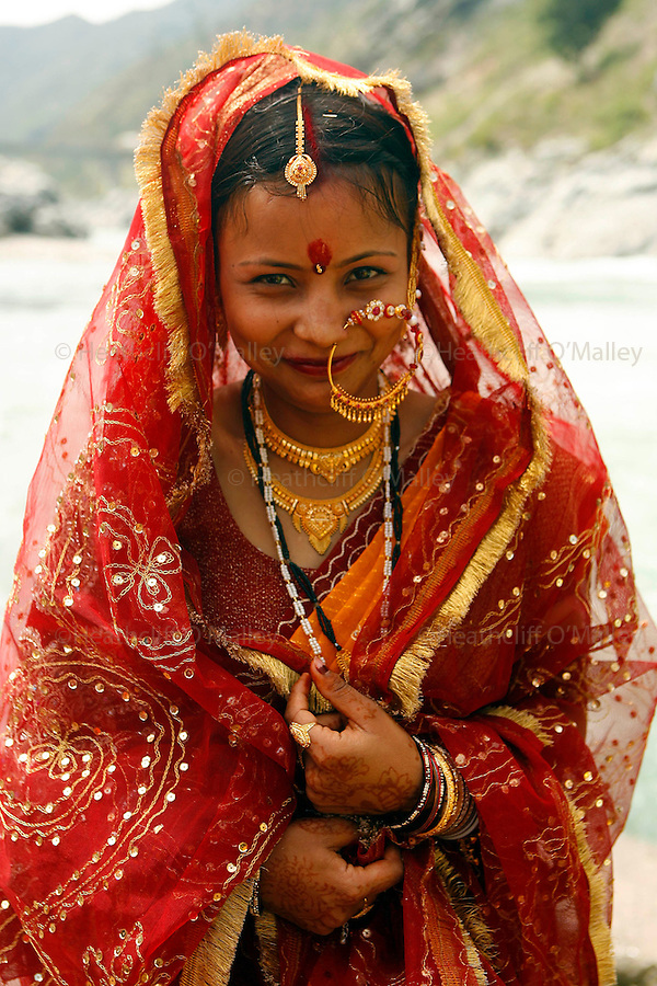 Newly wed bride Shalini Dhyani whose marriage has just been blessed by a Brahmin priest in the town of Devprayag a centre for pilrimage in the foothills of the Himalayas,and the confluence of Bhagirathia and Alaknanda tributaries, where the great river Ganges starts..The Ganges is 1557 miles long and stretches from the Himalayas to the Indian Port of Calcutta supplying water to one twelth of the worlds population. .  The Ganges is worshipped by the Hindu faith and is believed to be not only a source of life but also able to wash one's sins away, and Hindu's from across the globe make pilgrimage to the river referring to it as Ma Ganga.