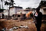 A Guatemalan prepares to lay flowers at a gravesite to celebrate Dia de los Muertos at Cementario General, in Guatemala City, Guatemala, on Tuesday, Nov. 1, 2011.