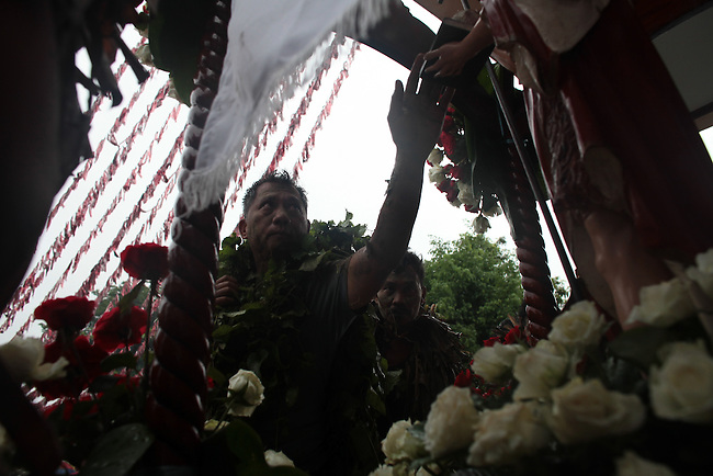 """A man touches a statue of St. John the Baptist during the annual Taong Putik, or """"mud people,"""" festival in Bibiclat, on Luzon island, Philippines. During the festival, devotees cover themselves in mud, banana leaves and other vines, which symbolize the animal skins that St. John the Baptist wore in the Bible. June 24, 2011."""