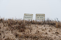 Two warning signs on a sand dune in East Hampton, NY