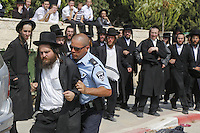 An Ultra-Orthodox Jewish man is pushed away by an Israeli policeman in Ramat Beit Shemesh West of Jerusalem on August 12 2013, after Several dozen of Haredim protest against desecration of ancient graves were discovered at a new housing construction site. Some 14 Ultra-orthodox Jews were arrested. Photo by Oren Nahshon