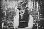 Portrait of a girl with a tophat in the forest behind a spiderweb