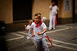 Two children playing in the street during the San Fermin Festival, on July 10, 2012, in Pamplona, northern Spain. The festival is a symbol of Spanish culture that attracts thousands of tourists to watch the bull runs despite heavy condemnation from animal rights groups . (c) Pedro ARMESTRE