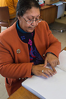 South Africa, Cape Town.  Editor Reading a Braille Student Workbook with her Fingertips.  Athlone School for the Blind.