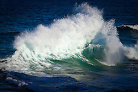 A wave creates a huge fan of spray cased by backwash off the cliff. Photo: joliphotos.com