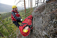 """Norwegian Air Ambulance training mountain rescue. A rescue paramedic is hoisted up with a """"patient"""" during a session at Torpomoen training center."""