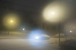 Merrick, New York, USA. January 24, 2015. A snowy town road is lit by street lights and the headlights of a car traveling during a snowfall in the middle of the night, shortly after 2 AM, in suburban Long Island, which is under a Winter Weather Advisory. 1-4 inches of snow could fall by 6 AM. Temperatures are 33º Fahrenheit, 0.56º Celcius.